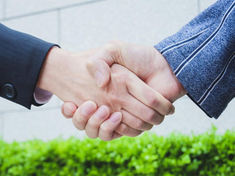 握手をする二人の人物